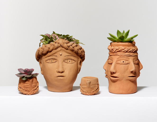 Four ceramic planters with carved faces