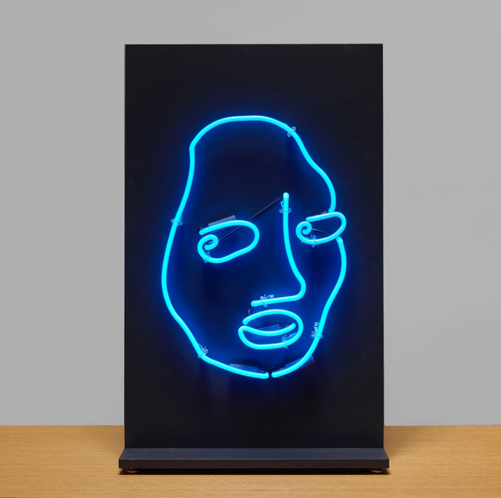 A blue neon light with a line drawing of a face design on a black background