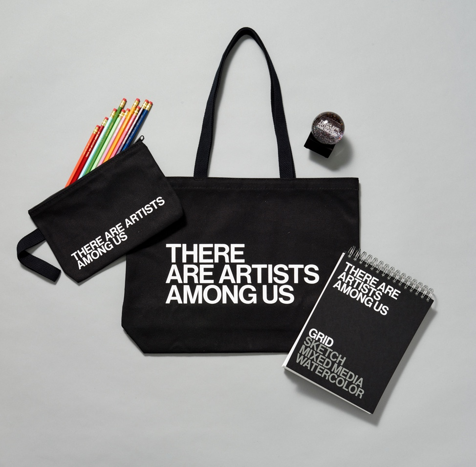 A small black canvas bag, a black tote bag, and black notebook with white text reading there are artists among us