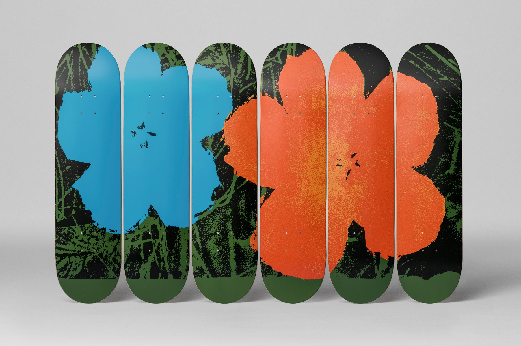 A group of skateboards with Warhol flower decals