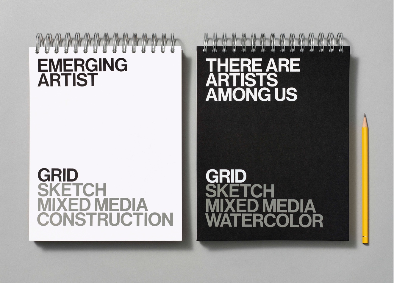 Two artist sketchpads, one white and one black, flanked by a pencil
