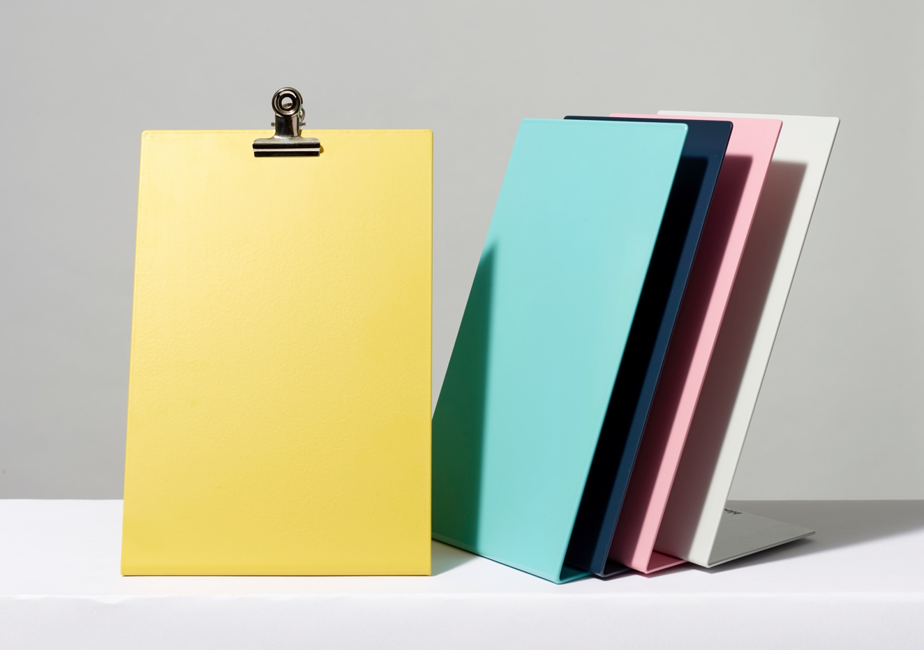 Five colorful clipboards leaning against one another