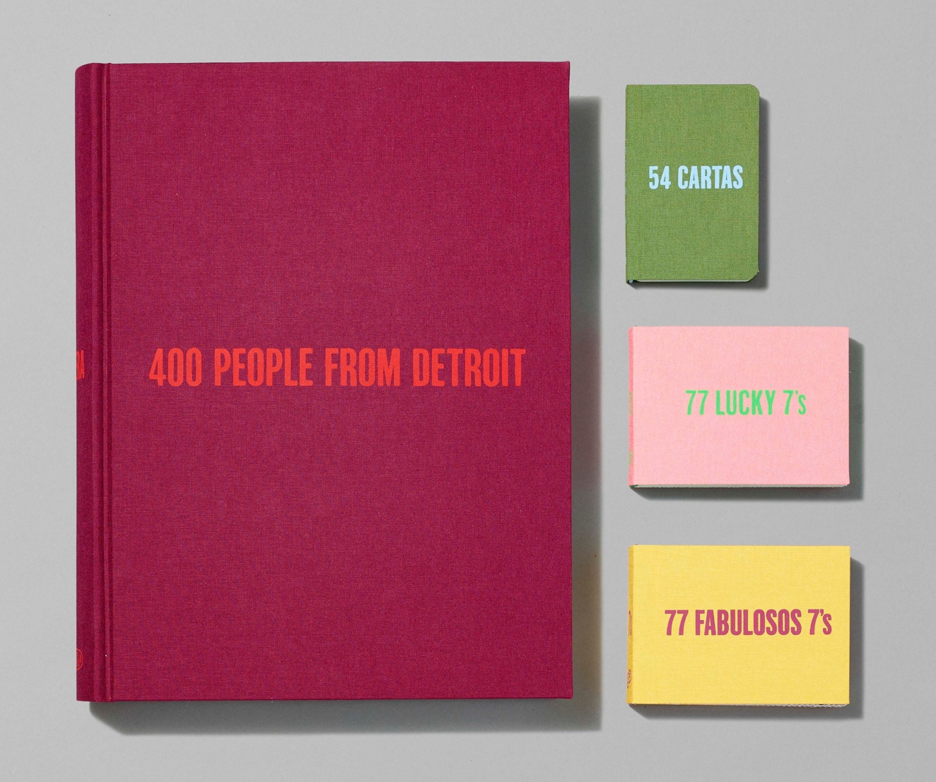 Four books of varying colors and sizes laid out in an artful grid