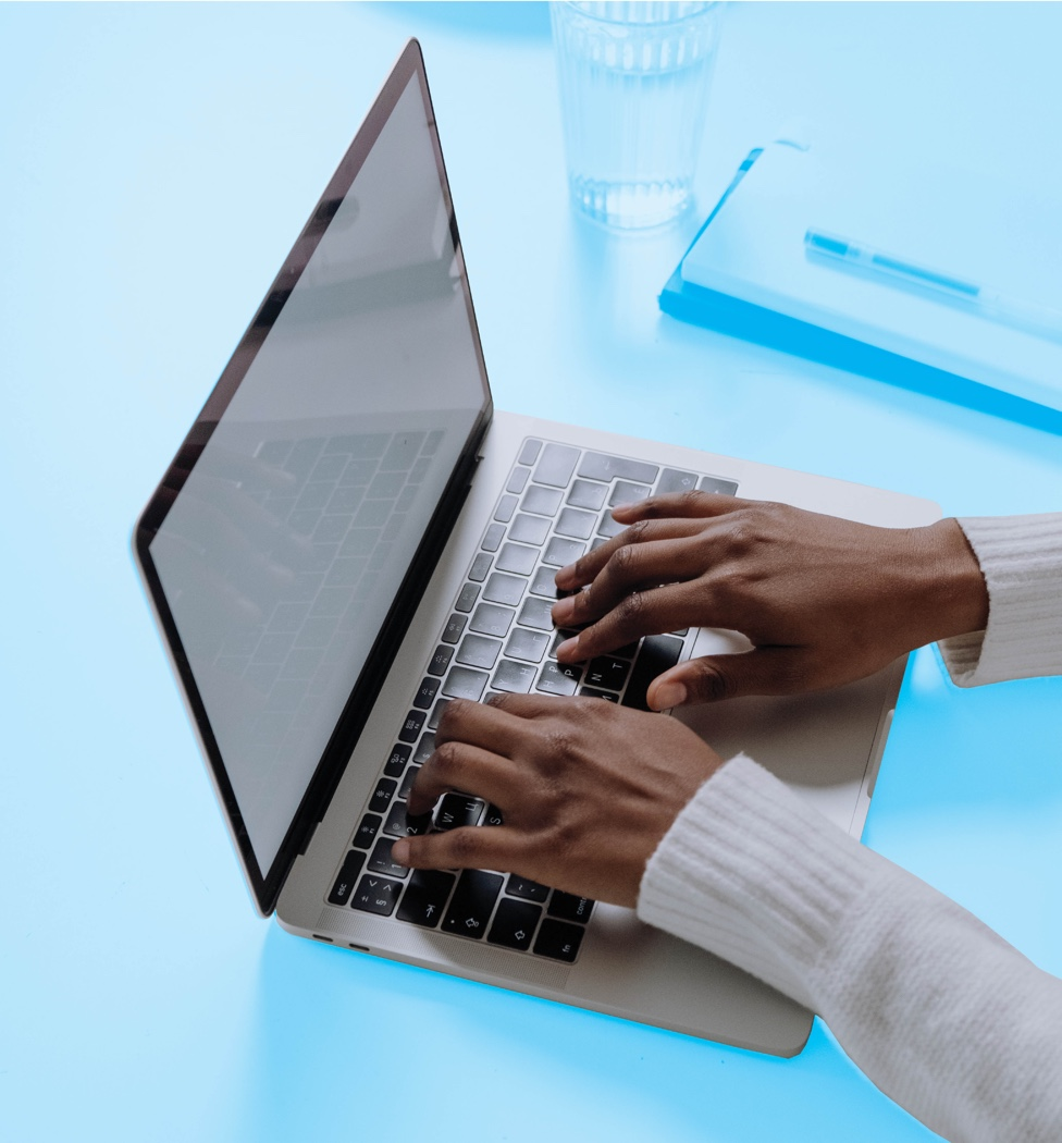 Someone's hands on a computer keyboard against a blue background